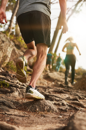 extreme angle: Closeup shot of a male runner on rough terrain outdoors. Trail running workout on hillside.