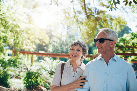 family walking: Portrait of happy mature couple standing together in a park and looking away. Mature caucasian couple admiring a view. Stock Photo