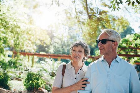 persona caminando: Retrato de la feliz pareja madura de pie juntos en un parque y que mira lejos. pareja caucásica madura contempla las vistas.