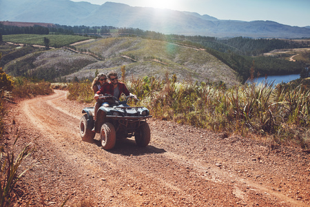 off road vehicle: Young couple having fun in the countryside while driving on a quad bike. Young man and woman enjoying off road vehicle ride on a summer day.