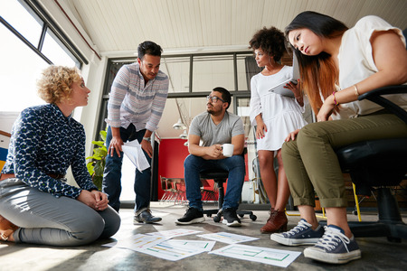 Group of young creative team going over some plans together. Documents laid out on floor with finalizing the design. Stockfoto
