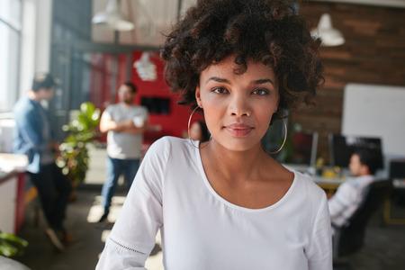 自信を持って若い女性デザイナー立っている彼女のオフィスで、バック グラウンドでいくつかの同僚との肖像画。若いアフリカの女性事務所に立っ
