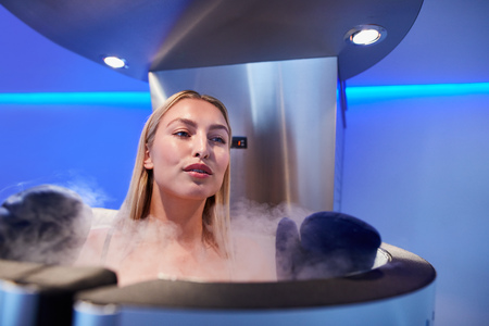 Young woman in a full body cryotherapy cabinet at cosmetology clinic. She is receiving skin treatment using cold nitrogen vapors.
