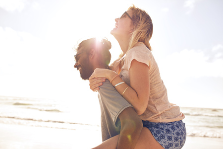 mixed couple: Side view portrait of young man carrying his girlfriend on his back at the beach. Man piggybacking girlfriend at seashore on sunny day. Stock Photo