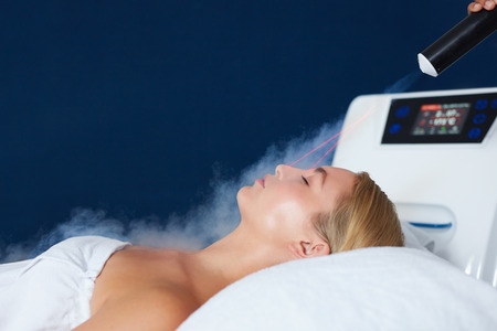 美容クリニックでレーザー フェイシャル トリートメントを得る若い白人女性のショットを閉じる。女性の受信側ローカル凍結療法療法。