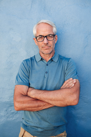 Portrait of a mid adult caucasian man standing with his arms crossed against a blue background. Caucasian male wearing glasses staring at camera.