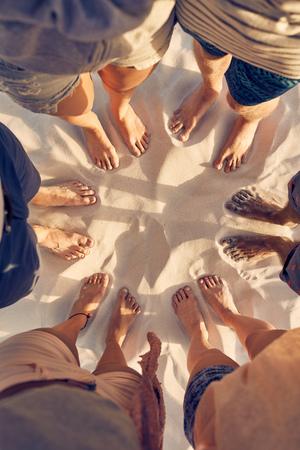 Вид сверху изображение разнообразной группы друзей, стоя босиком по кругу на песчаном пляже. Ноги молодых людей, стоящих в кругу. Понятие единства в многообразии.