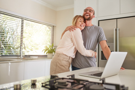 casual office: Portrait of happy woman embracing her husband in kitchen. Loving couple with laptop on  kitchen counter at home.