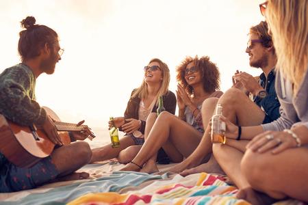 Gelukkig hipsters ontspannen en gitaar spelen op het strand. Vrienden drinken bier en luisteren naar muziek. Plezier op beach party in de avond.