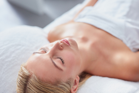 dayspa: Close up shot of attractive young woman lying with her eyes closed on a massage table. Caucasian woman at dayspa for skin treatment.