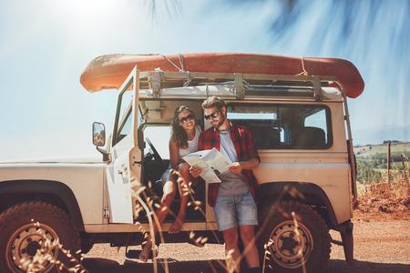 Pares novos que tomam uma pausa para olhar para um mapa durante uma roadtrip. Homem novo e mulher na estrada secundária à procura de indicações no mapa.