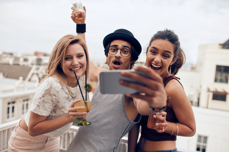Excited young people taking self portrait with mobile phone during a party. Happy young man and woman taking self portrait at rooftop party. Multiracial people having fun in party with drinks.