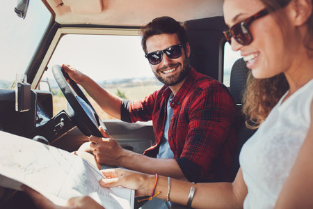 side road: Young couple sitting inside their car with map. Smiling young man and woman sitting together and looking at the map for directions. Stock Photo