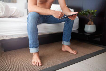 hombres jovenes: Recortar foto de un hombre joven que usa la tableta digital mientras se está sentado solo en la cama.