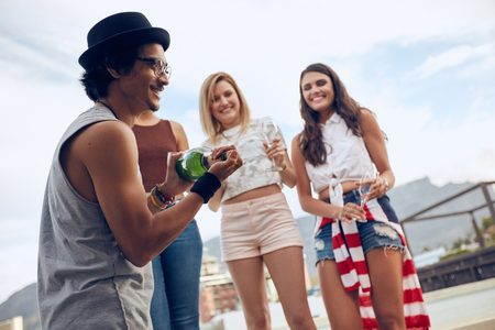opening party: Outdoor shot of young man opening a bottle of champagne with female friends standing in background by the pool. Young people having champagne at party.