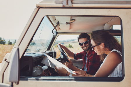 jeep: Man and woman on a road trip and reading a map together while seated inside their car. Happy young couple going on road trip.