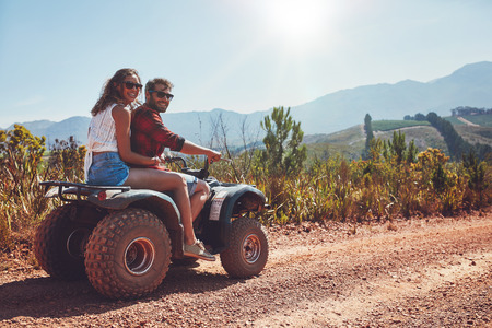 off road vehicle: Portrait of loving couple in nature on a off road vehicle. Young man and woman enjoying a quad bike ride in countryside. Stock Photo