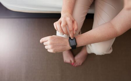 woman dialing phone number: Overhead shot of female hands using smartwatch. Close up image of woman using smart wrist watch in bedroom at home. Dialing a phone number. Stock Photo