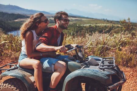 Homem e mulher se divertindo em uma aventura off-road. Casal andando em uma moto no campo num dia de verão.