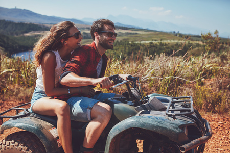 girlfriend: Man and woman having fun on an off road adventure. Couple riding on a quad bike in countryside on a summer day.