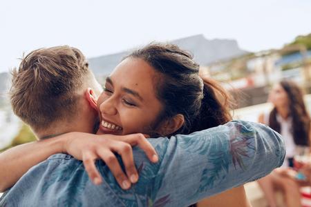 女性は彼女のボーイ フレンドに挨拶を採用します。若い女性のパーティーで彼女の友人を歓迎します。若い友人の屋上パーティーに到着します。 写真素材