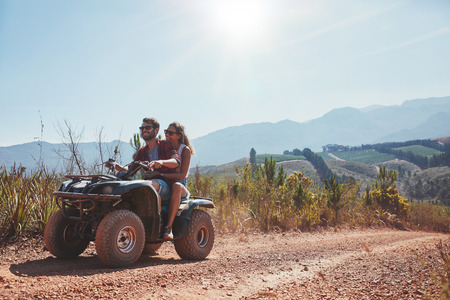 quad: Loving young couple enjoying a quad bike ride in countryside. Couple riding on an ATV.