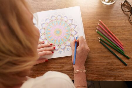Overhead view of woman drawing in adult coloring book with color pencils. Anti stress exercise at home.