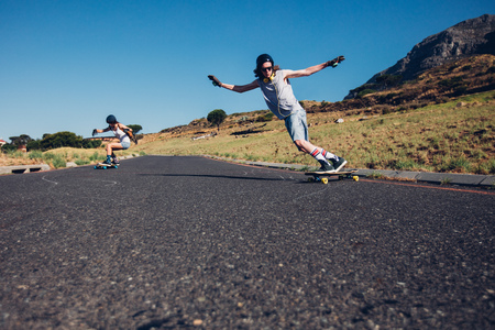 Young man and woman skateboarding on the rural road. Young couple enjoying skating on the road. Stock Photo