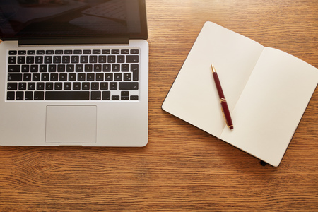 overhead shot: Top view shot of a laptop with diary and pen and on wooden table. Overhead view of working desk.
