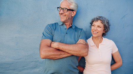 standing together: Portrait of a mature couple standing together and looking away and smiling against blue background. Middle aged man and woman leaning to a wall. Stock Photo