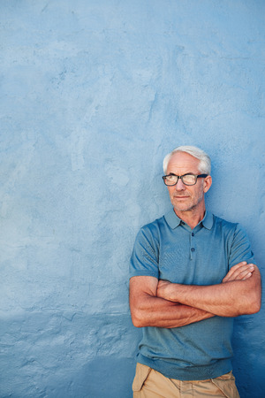 adult wall: Portrait of a mature caucasian man with glasses standing with his arms crossed against blue background. Mid adult man looking away at copy space against a wall.