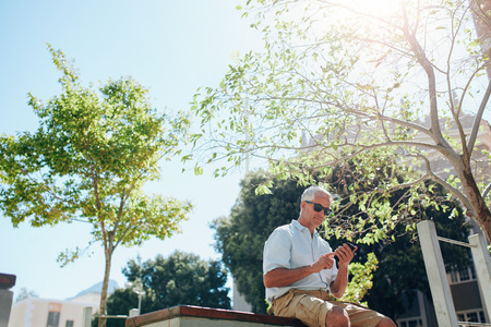 phone message: Low angle view of senior man sitting outdoors using cell phone on a sunny day. Mature tourist resting outside in the city and reading text message on his cell phone. Stock Photo