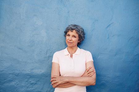 Portrait der schönen älteren Frau, die mit ihren Armen überquerte gegen den blauen Wand. Glückliche fällige Frau, die Kamera betrachtet.