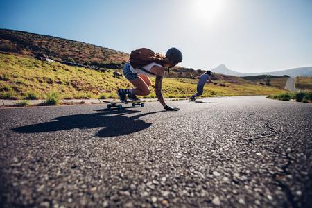Jonge vrienden schaatsen met hun skateboards op landelijke weg. Jonge mensen aan boord van de weg op zonnige dag.