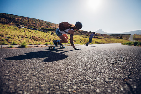 Young friends skating with their skateboards on rural road. Young people longboarding down the road on sunny day.