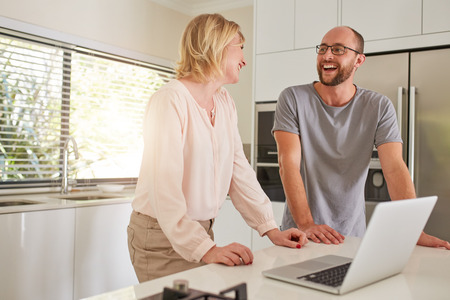 man with laptop: Indoor shot of a happy couple standing at kitchen counter with laptop computer. Man and woman looking at each other and smiling. Stock Photo