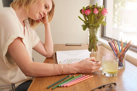 drawing table: Woman drawing an adult coloring book while comfortably sitting at table by a window. Stock Photo