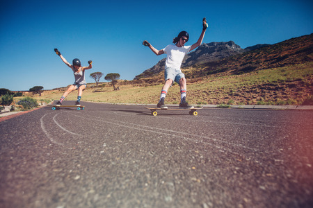 skateboarding: Young man and woman skateboarding on the road. Young couple practicing skating on a open road.