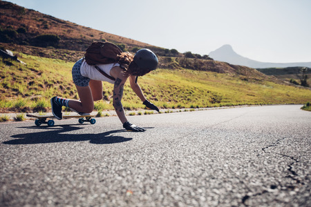 Rear view of young woman practicing skateboarding on rural roads on summer day. She is touching the road while doing stunts.