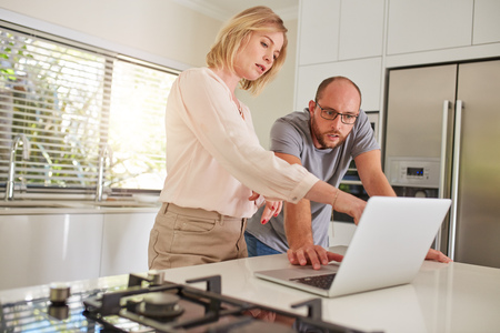 looking at computer: Portrait of mature couple working together on a laptop in the kitchen. Couple standing by the kitchen counter, with woman pointing at laptop.