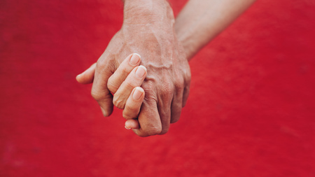 long lasting: Close up of man and woman holding hands against red background. Affectionate couple holding hands. Stock Photo