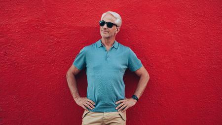 uomo rosso: Bel ritratto di uomo anziano in piedi con le mani sui fianchi guardando lontano copia spazio su sfondo rosso.