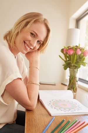 stress woman: Portrait of happy mature woman sitting at a table with adult coloring book and pencils colors. Caucasian woman relaxing at home with anti stress adult coloring book.