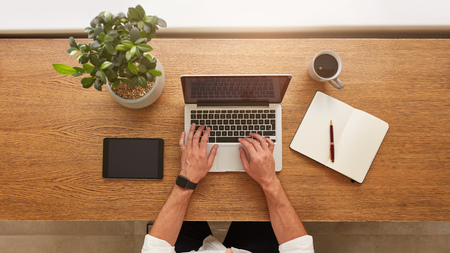 Direct boven visie op de menselijke handen te typen op de laptop. Laptop, digitale tablet, dagboek, kopje koffie en ingemaakte installatie op een bureau. Man werkt vanuit huis. Stockfoto