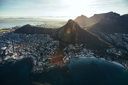 Birds eye view of city of cape town with beautiful beaches and mountain range on a sunny day. Aerial view of Cape Town city with Devils Peak. Banco de Imagens