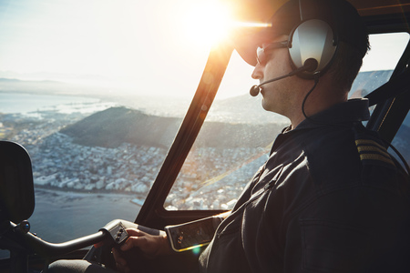 helicopter pilot: Close up of a male helicopter pilot flying aircraft over the Cape town city on a bright sunny day.