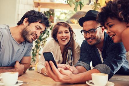 Группа молодых людей, сидя в кафе и, глядя на фотографии на смартфоне. Молодые мужчины и женщины, собравшиеся на кафе таблицы и с помощью мобильного телефона