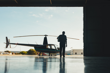 helicopter pilot: Rear view shot of pilot walking towards helicopter. Pilot and helicopter in a airplane hangar.