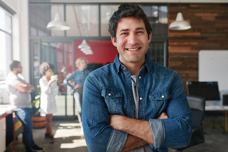 肖像英俊的年輕男子與他的手臂站在創意辦公交叉。自信的年輕男性的創意專業人士在看相機和微笑。