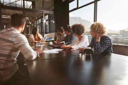 Jonge vrouw geeft een presentatie aan collega's op kantoor. Gemengd ras team van creatieve professionals in een vergadering op het kantoor. Stockfoto